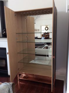 Custom white oak drinks cabinet with leather in lays, copper base, mirror back, 10mm glass shelves and wine glass rack.