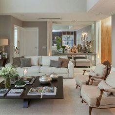 Sala de estar com mesa de centro preta, poltronas clássicas e sofá bege/creme. Parede cinza, tapete claro, e aparador com espelho ao fundo.