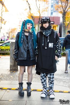Harajuku duo with girl wearing an all black fashion style with leather jacket, corduroy dress, fishnet stockings, platform boots, and black backpack; boy