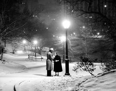 With the city lit up behind them, a couple wards off the cold by sharing a cigarette under a glowing street lamp in Central Park in 1957.