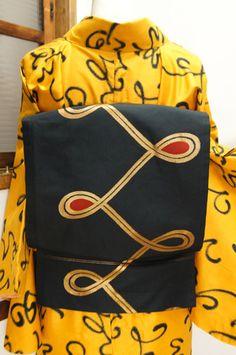 黒と金に赤をアクセントにリボンのような模様が描かれた名古屋帯です。