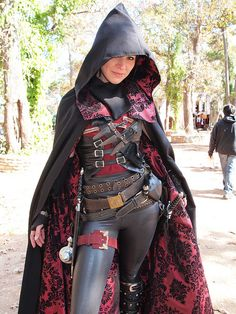 Rogue. Hooded cloak. Face mask. 4 belts across the waist and hips. Black catsuit under all. knee high boots. 2 daggers and scabbards. 2 pouches. Baldric with 2 sheathed darts. Short waist over bust corset front buckles. Leg belt with potion bottle attached. Thumb strip bracers. (Design Choice: Hood attached to front of costume).  From Steampunk - Kelsey Rademaker (by Joey Zepeda)