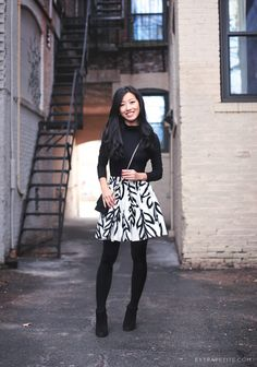 Patterned skirt with black turtleneck sweater, tights, and black booties