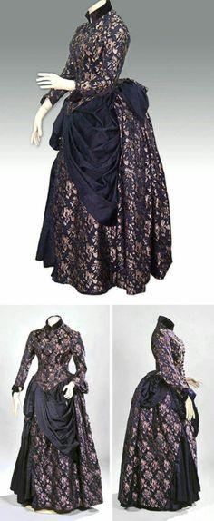 Dress ca. 1885. Silk brocade in purple and lilac. High purple velvet collar and trim at cuffs. Purple satin drapery on skirt.