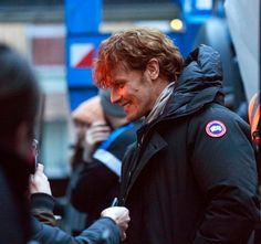 Sam grins as he talks to fans in the street
