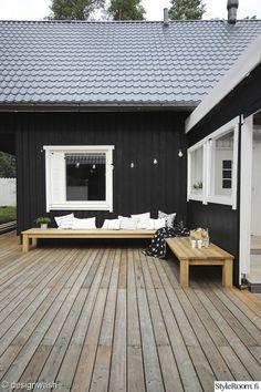 L字型に配置された木製の低いデイベッドのあるウッドデッキの屋外リビング2