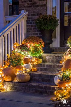 Check out this traditional fall porch decor with mums and pumpkins scattered across the front porch steps -- with twinkle lights as the cherry on top! Halloween Veranda, Halloween Porch, Fall Halloween, Diy Halloween Decorations, Spooky Decor, Fall Porch Decorations, Harvest Decorations, Thanksgiving Decorations Outdoor, Halloween Front Doors