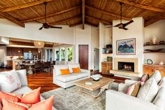 This airy living room features an open plan that allows for easy transition between the living, dining and kitchen areas. Exposed beam vaulted ceilings make the room appear larger, while a neutral color palette keeps the room light. Built-in flank the fireplace, while cherry hardwood floors add an exotic look to the space.