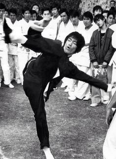 Bruce Lee kicking high on the set of Enter the dragon.