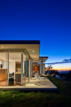 Stone and Glass  This contemporary residence is designed to seamlessly open unto the panoramic coastal ridge--‐top site via expansive operable glazed walls. T...
