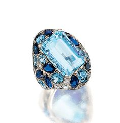 AQUAMARINE, SAPPHIRE AND DIAMOND RING, SUZANNE BELPERRON, 1950S. Of oblong form, set at the centre with a step-cut aquamarine bordered by oval and circular-cut similar stones, marquise-shaped sapphires, circular-, single- and brilliant-cut diamonds, mounted in platinum,