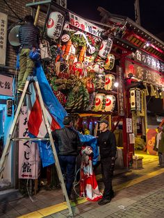 Asakusa Tori no Ichi 1/8 At the entrance of the Otori Jinja shrine in NW Asakusa/Senzoku, the  tobishoku workers are unveiling the big kumade, symbol of the fair/festival that will start in a few hours. #Asakusa, #Tori, #Ichi, #Kumade, #Otori, #Senzoku November 9, 2014 © Grigoris A. Miliaresis
