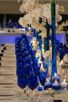Cobalt monaco blue glasses and vases with white orchids.
