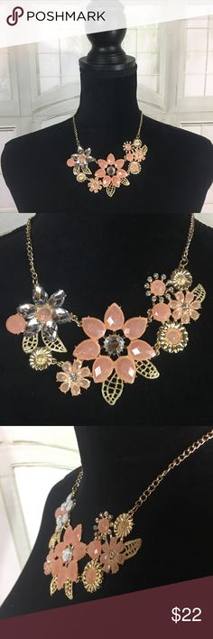 Flower Bib Necklace Pretty gold toned bib style necklace. Chain length is about 14 inches plus an additional extender. The flowers spread about 5 inches. New in package. Petals are a peach color with sparkles. Very pretty! Jewelry Necklaces