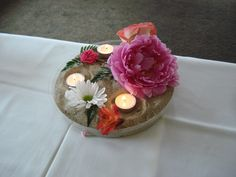 A flower arrangement I did for a friend's bridal shower.  Beach inspired with peonies, sand, candles
