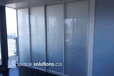 Custom aluminum-framed room divider with white lami glass by SpaceSolutions.ca