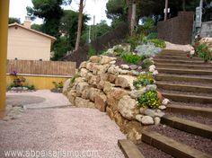 Un escalera de traviesas comunica la entrada de la finca con una zona de estar, un patio de adoquines inmerso en grava