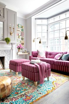 There are so many things to appreciate in this room. The repetition of the bold pink fabric, the collage on the wall, the bar cart, wall lighting and a great rug. Love it.