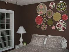 This is a creative solution to wall decor which brings color and pattern into a room, but the margins are annoying.  I would space the hoops wider and slightly lower so they don't sit so close to the ceiling.  An upholstered headboard would help, too, defining the dimensions of the bed so that whoever is sitting and reading in bed doesn't have to worry about the artwork falling on them if they lean back.