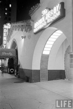 "The Vine Street Brown Derby restaurant, just down from the Hollywood and Vine corner. I love the glow of the Brown Derby Bamboo Room"" sign, but here's detail I've never noticed before: the octagonal pattern carved into the sidewalk out front. (1937)"