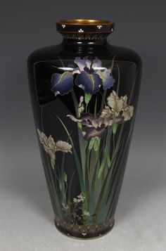 "Japanese Cloisonne Vase with Irises- A brilliant cloisonné vase worked in intricate techniques using various thicknesses of silver wires. On its dark ground, white and purple irises in full bloom burst forth from their brilliant green stems. On the reverse, a lone iris is captured in mid-bloom. Lappets and cherry blossoms on the neck and foot frame this beautiful scene of spring. This elegant cloisonne vase is in very good condition. Height, 12"". Meiji Period."