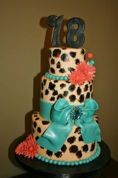 3 tiered cheetah print cake with fondant blue ribbon and pink flowers.