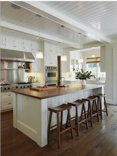 Love the dark wood and white for this kitchen with a big island