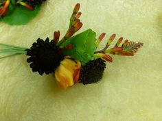 This garden style corsage creates lots of visual interest with contrasting colors and textures.  Adding a longer accent flower to your wedding flowers creates a flow the eye will follow making sure all your flowers get noticed!