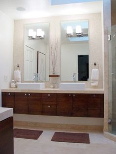 Love the wall tile, the raised sinks, the floating cabinets! Sconces on a mirror...who would have thought?!