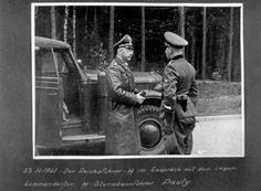 Stutthof, Germany, Himmler conversing with the camp commandant, SS Sturmbannfuehrer Pauly, next to his car.