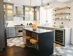 Fabulous gray kitchen features gray cabinets painted Benjamin Moore Cinder adorned with brass pulls, Schoolhouse Electric Card File Pulls in Natural Brass, topped with white quartz and a square white brick tiled backsplash.