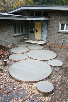 I LOVE this circular walkway. They let grass grow up between the circles, but I would use gravel or sand and tamp it down like you do with brick. Really unique! jh