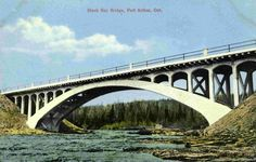 https://flic.kr/p/qBkxFc | Black Bay Bridge, Port Arthur | Description: After the Post Office approved the mailing of illustrated postcards in 1897, many hand-coloured images of the city were produced, purchased, and mailed to friends and loved ones. This postcard depicts one of the two bridges of historic significance in what was then Port Arthur. Black Bay Bridge is a reinforced concrete single-span structure - the first of its kind in North America when it was built in 1911. Accession ...
