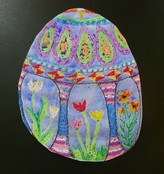 use oil pastels to make a resist painting. make it shaped for whichever season or theme you are working on. for this one, the drawings on the egg shapes are based on ukranian decorated eggs.