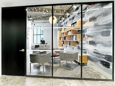 WME/IMG's Office by the Rockwell Group Lets Talent Shine  Steel-framed glass fronts a partner's office with custom shelving. Photography by Eric Laignel.