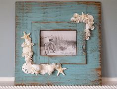 Beach decor distressed aqua seashell frame. This beautiful new nautical decor 15 square shell frame is made on reclaimed barnwood painted in a distressed beautiful beachy aqua turquoise. Absolutely yummy for beach decor! It holds a 5x7 photograph at its center and is a nice large 15 square for a great wall photo. Each wood frame will be unique and may have distressed parts, it is real reclaimed barn wood. Gorgeous corner clusters of pearly white shells and tiny little white knobby starfish…