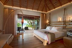 Privacy and natural light is managed with sheer drapes, screens, and of course sliding glass doors. Сonstance Moofushi Resort. Island Architecture.