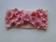 Faixa na meia de seda salmon com aplicação de flores em feltro e miolo de pérolas. R$ 21,00