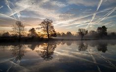 Contrails reflected in a lake in Langley Country Park, Slough, Berkshire Picture: Kevin Day/Alamy