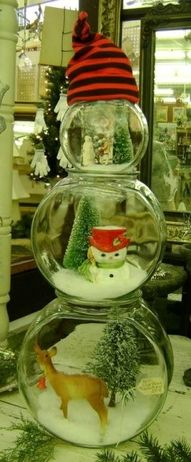 Three sizes of fishbowls stacked to become a 'snowman' and filled with Christmas 'stuff'' then topped with a stocking cap.