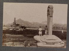 A stone sculpture of a turtle (bixi) with a column (stelae) rising out of its back. Two Korean children play on the base. The sculpture sits in an empty area, a low brick wall and neighborhood in the background. Korean Peninsula, Stone Sculpture, Historical Images, Old Pictures, Magick, Kids Playing, The Book, The Neighbourhood, Japanese