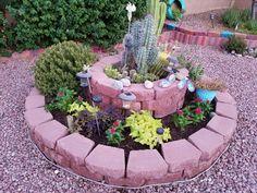 Raised flower beds containing drought tolerant plants on top. Rosemary, potatoe vines abs Vincas below.