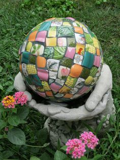 In its former life it was a bowling ball until it was covered with old dishes!  The hands, bought from a local garden center, and intended for bird seed, make a great holder.