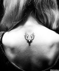 Tête de cerf noir, sur le haut du dos.  ↟↟