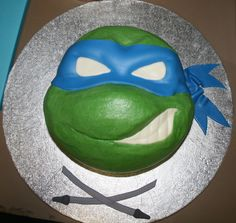 "Leonardo - A Ninja Turtle cake for my little brother's 6th birthday.  I used an 8""round carved, and a 4"" round carved for the nose.  The cake is covered in crusting BC and I used a fondant/gumpaste mix for the mask, eyes, teeth and katanas."