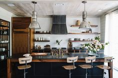 Two restored vintage factory lights hang above the central island. The island stools are repurposed vintage schoolhouse chairs. Two restored vintage factory lights hang above the central island. The island stools are repurposed vintage schoolhouse chairs. Industrial Kitchen Design, Vintage Industrial Furniture, Industrial Interiors, Industrial House, Interior Design Kitchen, Rustic Industrial, Industrial Kitchens, Industrial Lighting, Industrial Windows