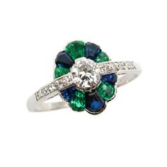 Art Deco diamond, emerald and sapphire cluster ring, c.1925  , centred by a round brilliant cut diamond to a shaped oval surround set with alternating calibrй cut sapphires and emeralds, a line of single cut diamonds either side, mounted in platinum