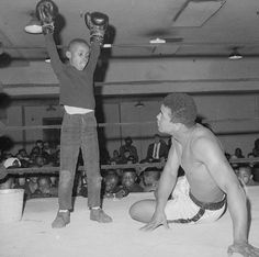 "Keith Green, nine-year-old fourth grader from P.S. 175 in Manhattan, is shown striking a victorious pose after ""flooring"" heavyweight champion Muhammad Ali at Madison Square Garden in New York, March 14, 1967, as Ali trained for his March 22 bout with Zora Folley. Keith was among 300 children from P.S. 175 who visited Ali. (AP Photo/John Lindsay)"