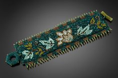 William Morris Floral Cuff by Julie Powell. Inspired by the ornate textile designs of artist William Morris, this intricate beaded cuff is embroidered and woven by hand using simply a needle and monofilament thread. Lustrous Czech glass seed beads are interspersed with labradorite and amazonite. Hand-beaded toggle closure and soft Ultrasuede backing. Limited quantity of 25.