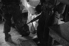 Soldados puxam um suspeito Viet Cong de seu esconderijo durante uma varredura através de uma aldeia vietnamita. Nomes, data e local desconhecidos.